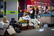 06-10-2012 - A man rests in a box with a can of beer, East Street Market, Walworth, London. © Connor Matheson