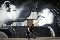 30-07-2014 - A young couple walking past a mural on an abandoned shop front. Rotherham centre, South Yorkshire. © Connor Matheson
