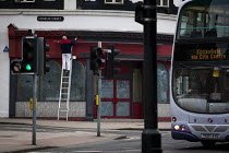 03-15-2015 - A man painting the outside of an empty shop while a bus is driving past. Sheffield, South Yorkshire. © Connor Matheson