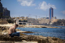 04-22-2015 - A local workman relaxes by the sea while listening to his Ipod with the Hilton Hotel and Sain julians in the background. Sliema, Malta. © Connor Matheson