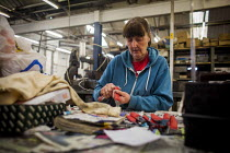 18-05-2015 - A female worker trimming excess plastic from the handle's of the newly made cooking knives. J Adams and Sons manufacture a range of military and cooking knives out of steel using traditional hand base... © Connor Matheson