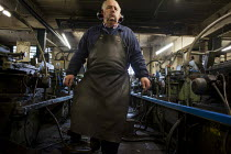 18-05-2015 - A worker maintaining a machine that sharpens steel. J Adams and Sons manufacture a range of military and cooking knives out of steel using traditional hand based production methods. The family busines... © Connor Matheson