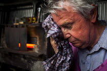 18-05-2015 - A worker cooling himself down due to the heat from the furnace. J Adams and Sons manufacture a range of military and cooking knives out of steel using traditional hand based production methods. The fa... © Connor Matheson