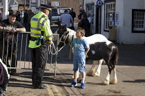 05-06-2015 - Appleby Horse Fair, Cumbria, young boy asking a policeman to look after his ponies. © David Mansell
