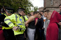06-06-2015 - Appleby Horse Fair, Cumbria, Police Officers arresting a man for starting a fight. An argument developed over the man buying a red convertible Porsche from another Traveller. © David Mansell