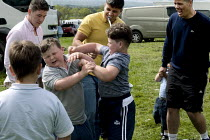 07-06-2015 - Appleby Horse Fair, Cumbria, Gypsy fathers encouraging bare fist boxing, boys learning physical pain and the skills of protecting yourself by fighting. © David Mansell