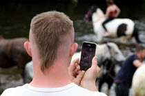 05-06-2015 - Appleby Horse Fair, Cumbria, a young man who has Down syndrome using his phone camera to record the horses being washed in the River Eden © David Mansell