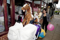 20-05-2015 - Wickham Horse Fair a traditional one day annual event, Hampshire. A young mother outside a baby clothes shop with a huge soft toy horse with help from her mother holding the families new born baby. © David Mansell