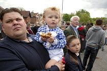 20-05-2015 - Wickham Horse Fair a traditional one day annual event, Hampshire. A father with his two children, eating a beefburger, watching the horses. © David Mansell