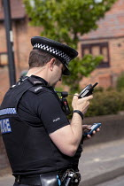 20-05-2015 - Wickham Horse Fair a traditional one day annual event, Hampshire. Police Officer working with RSPCA and trying to find the mobile telephone number of a driver who had left his dog in a van with insuff... © David Mansell
