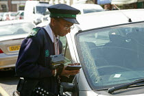 09-05-2005 - A young man working as a car parking meter attendant, who is employed by the London Borough of Hillingdon, checking the details of parked cars in Ruislip, High Street, London. © David Mansell
