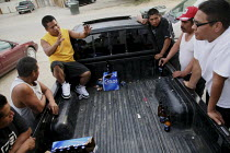 11-06-2009 - Alberto Garcia talks with other men as they drink beer, discuss work and relax around a pickup truck after work. A community of a few hundred migrant indigenous Mixtec farmworkers from Oaxaca live in... © David Bacon