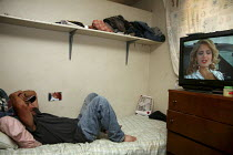 04-08-2010 - Watching TV. Mexican migrant farm workers living in a dormitory labor camp on the Martinelli ranch, Graton, California. These workers are H2A guest workers under contract for six months. After their w... © David Bacon