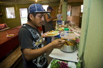 04-08-2011 - Families live in the Royce Bone labor camp in Nash County. These migrant families come from Mexico, mostly Veracruz, and work in the fields of tobacco and sweet potatoes. Workers get dinner in the cam... © David Bacon