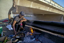09-09-2014 - Tijuana, Mexico - Homeless people have set up a camp in the riverbed of the Tijuana River, in downtown Tijuana, not far from the U.S. Mexico border. Juan Guerra, a Zapotec migrant from Oaxaca, cooks a... © David Bacon
