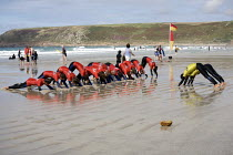18-08-2010 - Surfing instructor with beginners, stretching, Surf School, Sennen Cove, Cornwall © Duncan Phillips