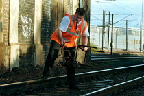 17-12-1999 - Railway worker on anti vandalism patrol removes debris thrown onto the tracks. This type of vandalism increases during school holiday periods so a dedicated team patrol the tracks to prevent and clear... © Duncan Phillips