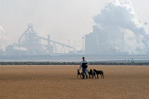 24-03-2003 - Against the background of the steel Industry on Teesmouth, the Corus Teesside steelworks, a man walks his greyhounds on North Gare Beach Hartlepool. © Geoff Crawford