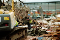 02-03-2003 - Demolition worker moving debris by hand amongst mechanical diggers as the previous High School is demolished. The new school building can be seen behind, the land will be used for housing. Stratford o... © John Harris