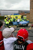 20-09-2003 - Children watching an emergency services attend a simulated road traffic accident at a fire and ambulance station open day. They are cutting open the car to get a victim out. © John Harris