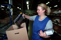 16-12-1999 - Women worker packing books into cardboard box on a production line at OUP automated print distribution centre Corby © John Harris