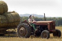 06-08-2003 - Farmworker driving a tractor and trailer, bringing in the harvest. Warwickshire. He is drinking a bottle of water. © John Harris