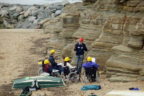 21-07-2007 - Geologist lecturer from Durham University lecturing on the Jurassic coastline to disabled Open University students during a field trip, Staithes, North Yorkshire. © John Harris