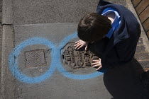 08-05-2009 - A child studying a water services inspection cover. Pavement markings showing the location of utilities underground prior to roadworks. Due to the huge number of utility services located within the ro... © John Harris