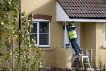 10-11-2010 - A worker fittting a porch. New homes being built on an estate, West Wick, Weston-super-Mare © John Harris