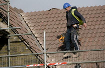 10-11-2010 - A worker cutting tiles on a roof. New homes being built on an estate, West Wick, Weston-super-Mare © John Harris