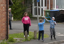 19-05-2013 - Boys playing, dueling with lightsabers on the street corner outside their house, watched by their big sister. Stratford upon Avon © John Harris