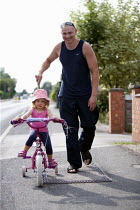 18-07-2013 - Proud father taking his little girl out on her new bike, with stabilisers. Migrant worker with his daughter born in the UK. © John Harris