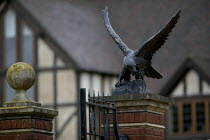 22-10-2013 - One of a pair of bronze gatekeeper sculptures depicting a bird of prey hunting above the automatic gates of a newly built mock Tudor mansion, Ullenhall, Warwickshire. © John Harris