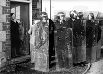 01-02-1985 - Miners Strike 1985. Riot police occupying pit village to get scabs out. Houghton Main, Yorkshire. Women in the doorway of the corner shop watching riot police with long shields © John Harris