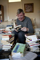 03-08-2014 - John, a disabled schizophrenic who hears voices, at home with his books which he reads avidly. His benefits have been reduced by the bedroom tax as his flat has a spare room. Stratford upon Avon, Warw... © John Harris