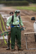 11-07-2014 - A farmworker wearing protective clothing (Waterproof Spray Suit) training in the use of a backpack Pesticide applicator, Warwickshire © John Harris