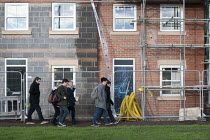 18-12-2014 - Students walking to college past new housing nearing completion which they may never be able to afford, Stratford-upon-Avon, Warwickshire © John Harris