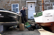 21-03-2015 - Fishermen repairing an engine of a fishing boat, Mousehole harbour, Cornwall © John Harris