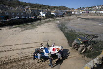 21-03-2015 - Tractor and fishermen launching the fishing fleet at the start of the season, Mousehole harbour, Cornwall © John Harris