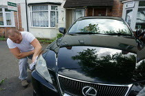 30-05-2015 - Polish migrant worker cleaning and polishing his Lexus car outside his rented accommodation, his daughter is watching. Stratford Upon Avon. © John Harris