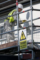 11-06-2015 - Danger men working overhead sign. British Gas workers insulating houses to reduce enegy consumption, Evesham © John Harris