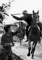 18-06-1984 - Mounted Policeman attacking Lesley Boulton Orgreave 1984. Police mounted on horseback attacking Lesley Boulton from miners womens support group WAPC. Battle of Orgreave, Orgreave coke works mass picke... © John Harris