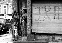 04-10-1988 - Asian women talking outside a street corner shop with IRA graffiti in poor Inner city area of multiple deprivation Sparkhill Birmingham 4/10/1988 © John Harris
