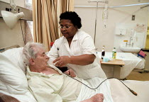 13-01-1999 - Health Care Assistant Auxiliary Nurse helping patient to drink in geriatric care unit. Hospital Birmingham © John Harris