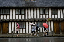 10-09-2011 - Walking past the 15th-century Elizabethan Almshouses provided by The Guild of the Holy Cross. Tourists visiting historic Stratford on Avon in the rain. The British Summer © John Harris
