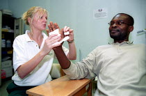 07-08-2002 - Tess Hogg Unison member and Occupational Therapy Clinical Specialist in hand injuries treats patient with crush injury. He was injured two years ago in his job as a Mechanical Engineer, and is recover... © Jess Hurd