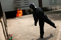 22-06-2004 - Police officer demonstrates the use of a petrol bomb at a Prime Training Solutions, Public Safety Awareness Course for journalists. Greater Manchester Police training facility, Claytonbrook Complex. G... © Jess Hurd