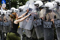 15-06-2011 - A young woman pushing riot police shields. Confrontations between police and protesters outside the Greek parliament during a general strike against austerity cuts. Syntagma Square, Athens, Greece. © Jess Hurd