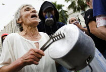 15-06-2011 - An elderly women banging a pot joins protesters outside the Greek parliament as the trade unions hold a general strike against IMF imposed austerity measures. Syntagma Square, Athens, Greece. © Jess Hurd
