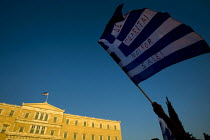 19-06-2011 - Demonstrators outside the Greek Parliament with Not For Sale on a Greek flag. Against austerity cuts. Syntagma Square, Athens, Greece. © Jess Hurd